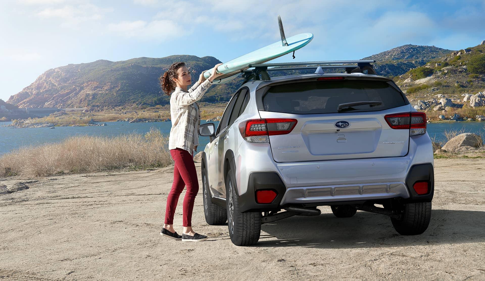Une femme pose une planche de surf sur un Subaru Crosstrek 2021
