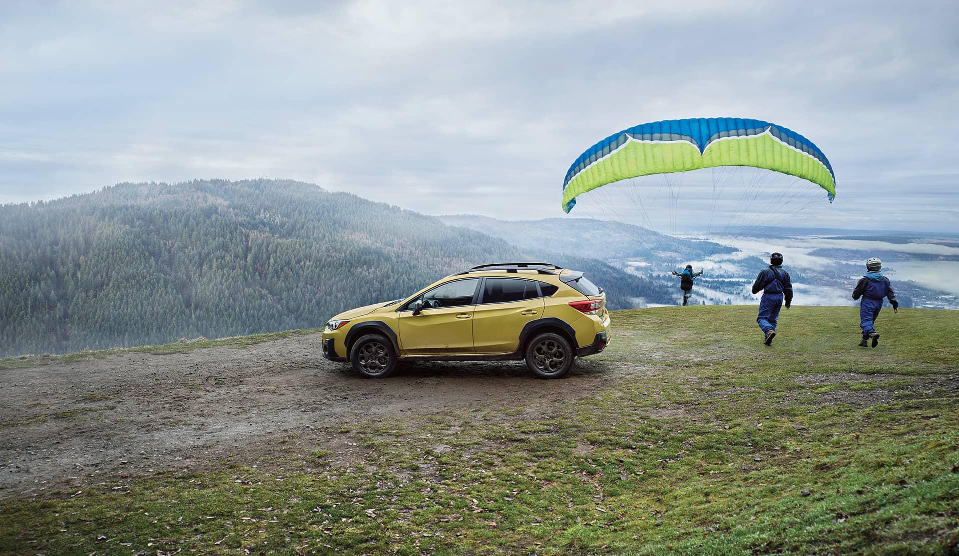 Subaru Crosstrek 2021 jaune de côté et des gens qui font du parapente