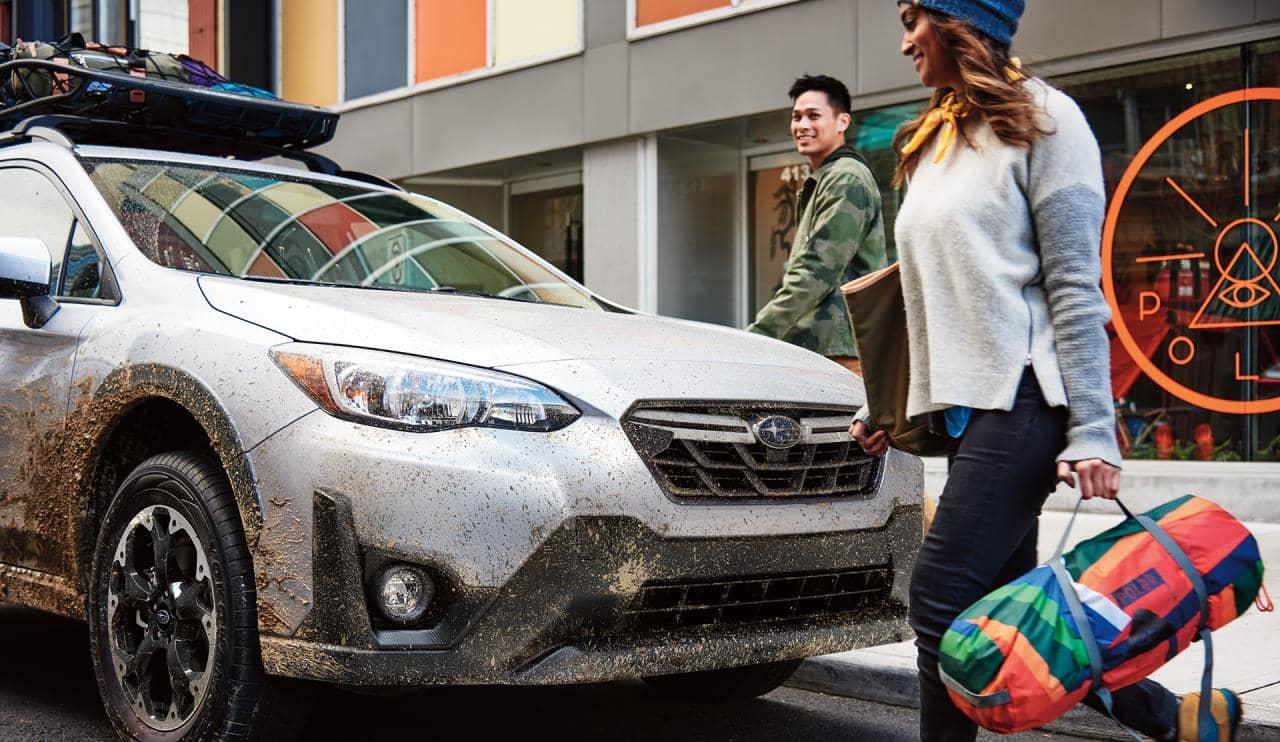 Deux personnes devant le Subaru Crosstrek 2021 enduit de boue