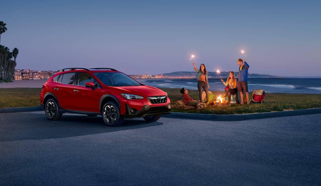 Une famille autour d'un feu de camp près du Subaru Crosstrek 2021